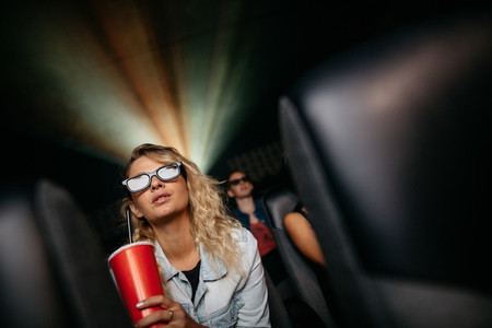 Beautiful woman watching 3d movie in theater