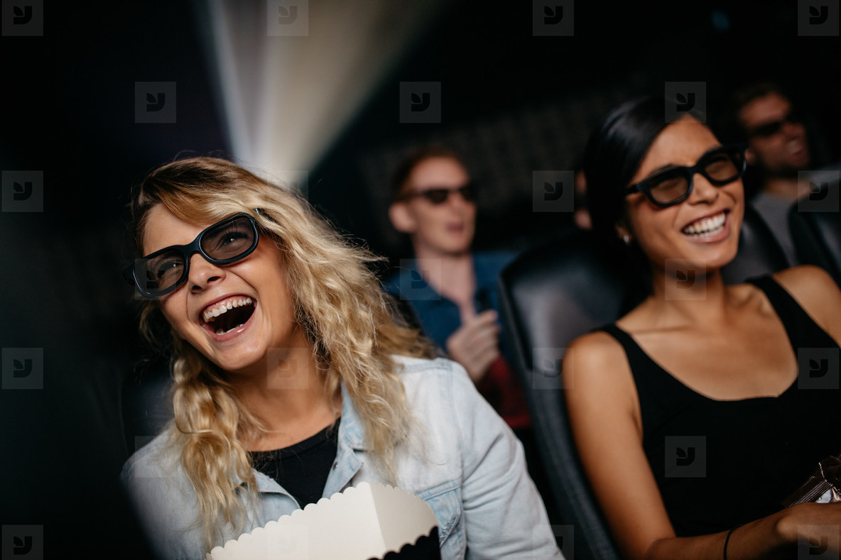 Female friends watching 3d movie and laughing