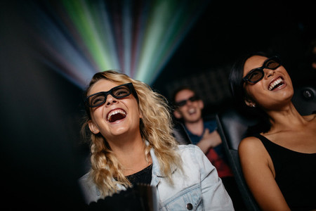 Smiling female friends watching 3d movie