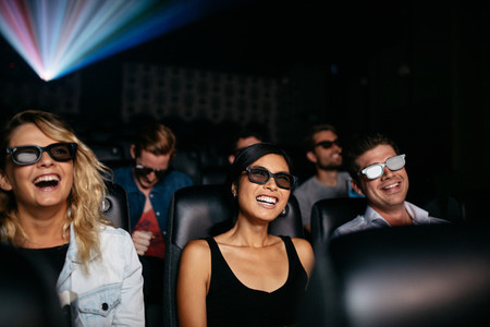 Friends watching 3d movie in theater and laughing