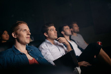 Young friends watching movie in cinema hall