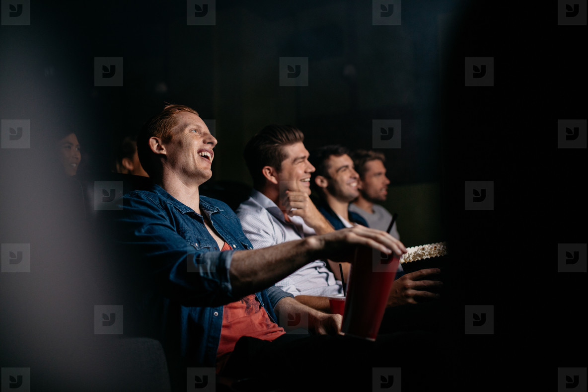 Young people watching comedy movie in theater