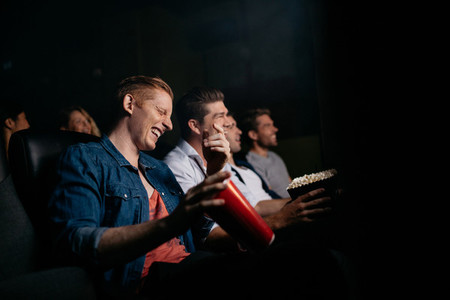 Young man with friends watching comedy movie