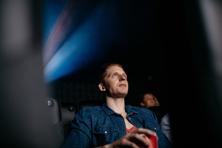 Young man watching movie in cinema