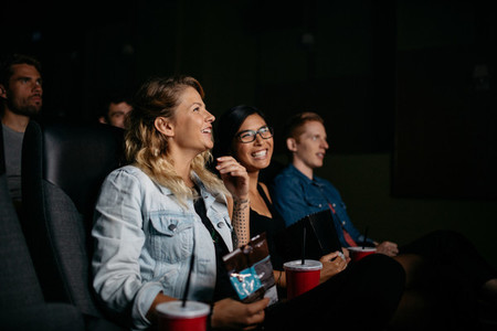 Happy young people watching movie in cinema