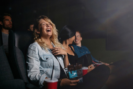 Young people watching movie and laughing