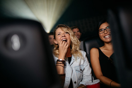 Smiling young women watching movie in theater