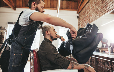 Barber putting salon cape to client