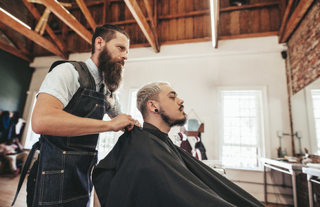 Barber serving client in hair salon