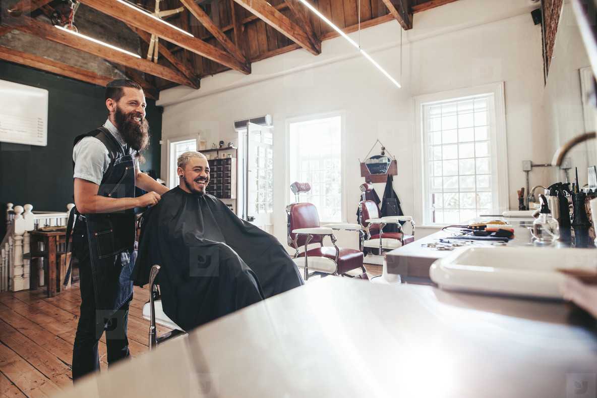 Hairdresser with client sitting at salon and smiling