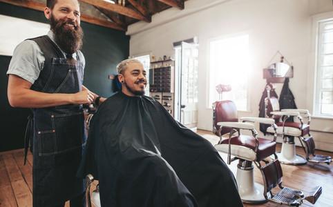 Hipster man getting haircut at barber shop