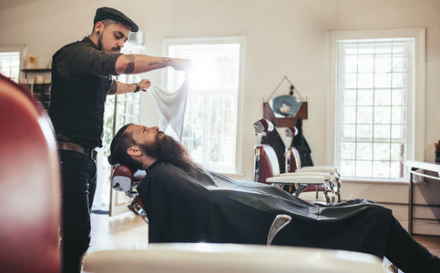 Barber taking care of client in barbershop