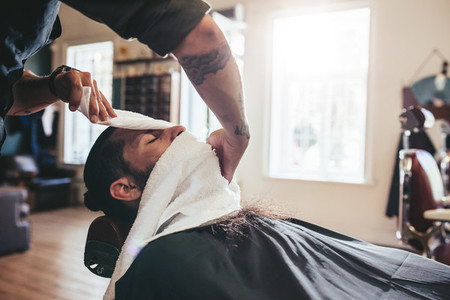 Hairdresser covering face of client with towel