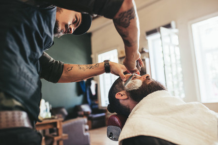 Professional barber shaving customer