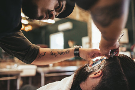 Barber shaving bearded man