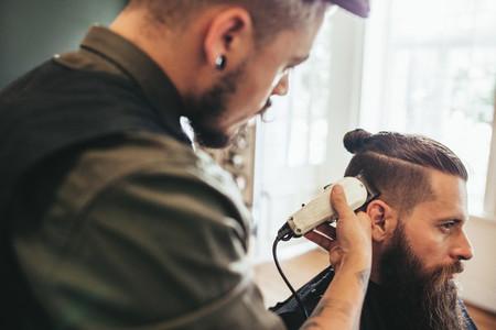 Hairdresser cutting hair of customer at salon