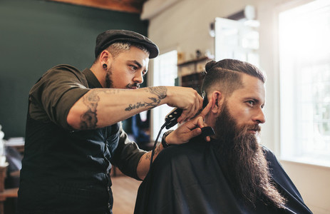 Man getting trendy haircut in barbershop