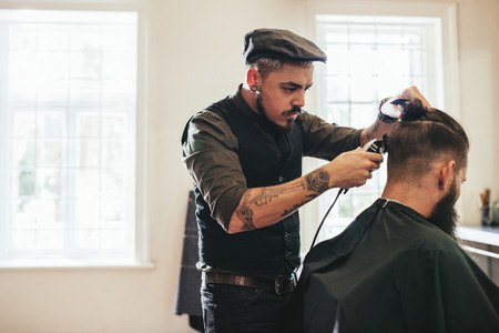 Hairstylist cutting hair of customer at barber shop