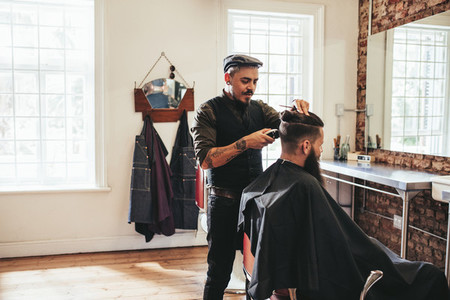 Male barber giving client haircut