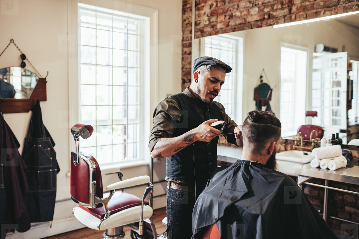 Young man getting trendy haircut at barbershop