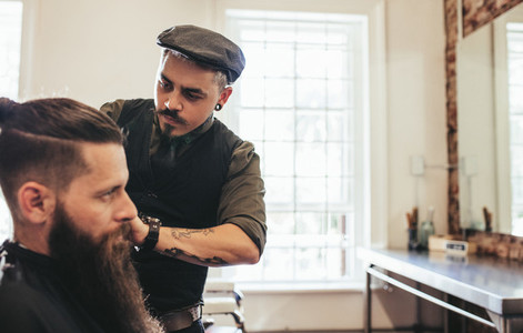 Stylish hairdresser serving client at his shop