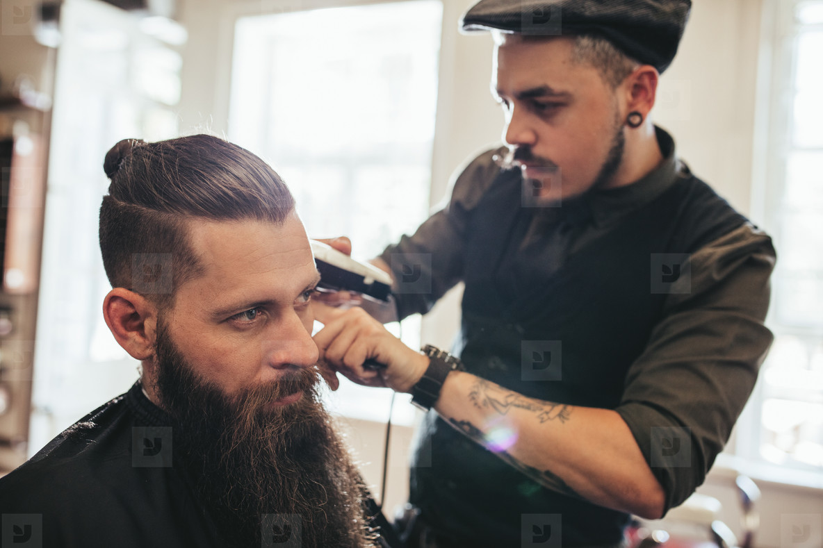 Young bearded man getting haircut in salon
