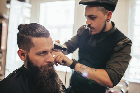 Young bearded man getting haircut in salon