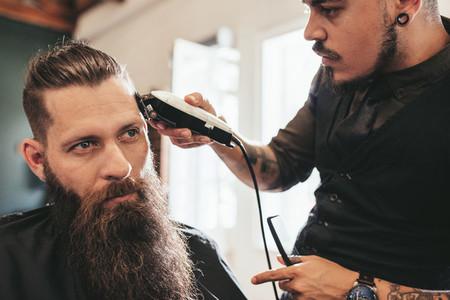 Young man getting trendy haircut at salon