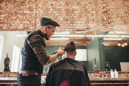 Hairdresser cutting hair of client