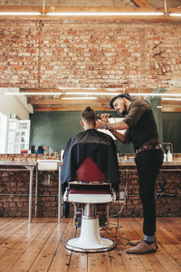 Male hairdresser trimming hair of customer