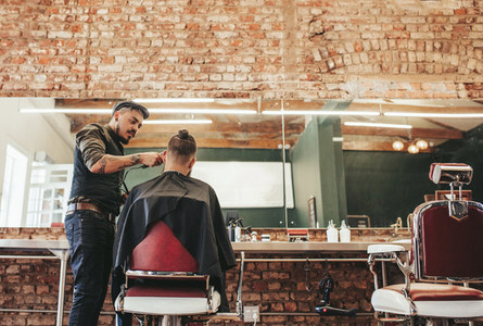 Stylish barber giving haircut to client