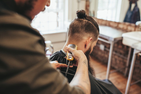 Man getting haircut by barber at salon