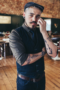 Stylish young male barber in barbershop