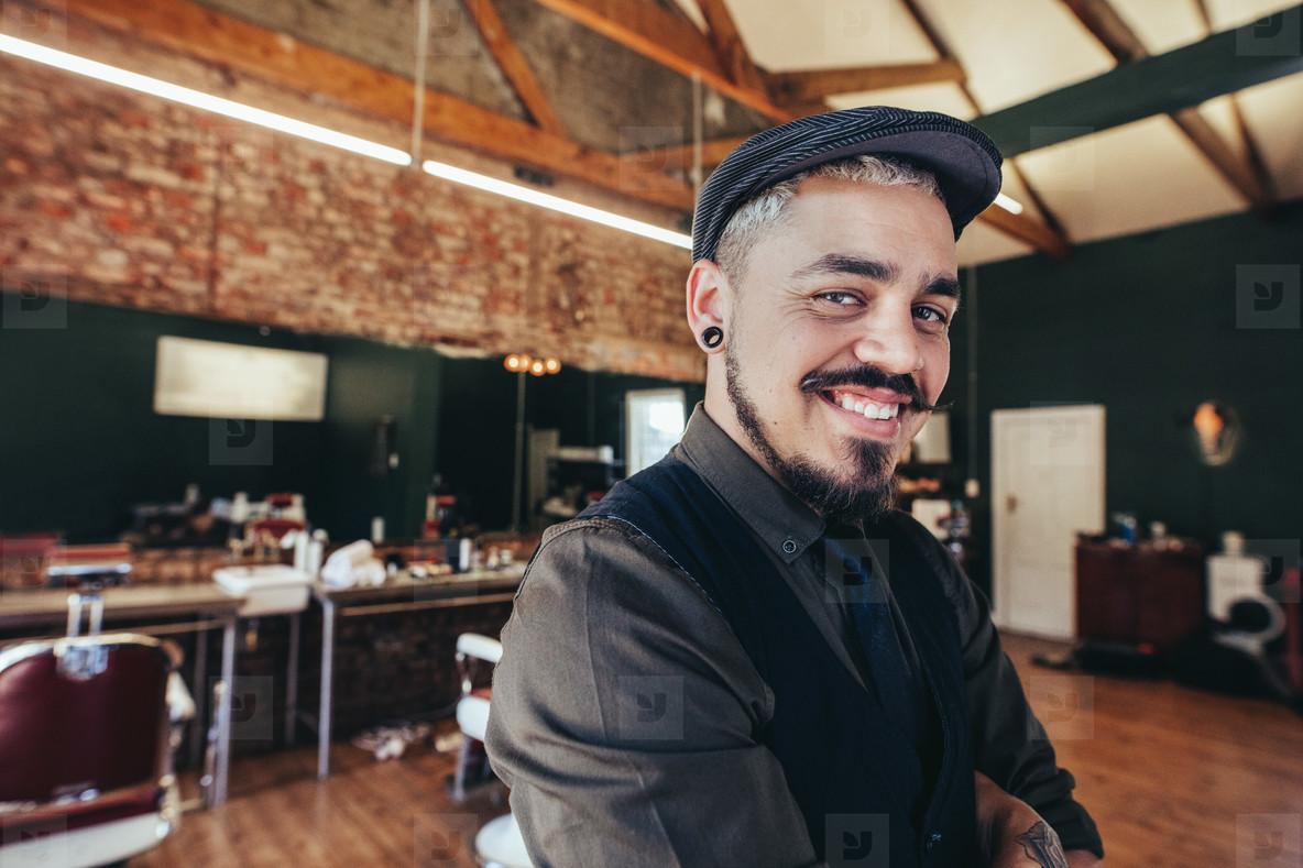 Handsome hairdresser smiling at barbershop