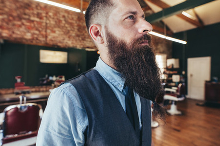Serious male barber with long beard