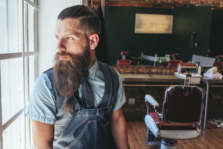 Barber standing by window and looking away