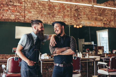 Happy barber with client standing at barbershop