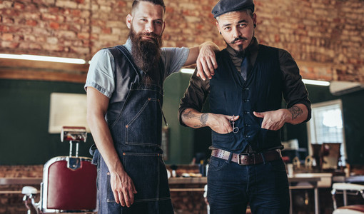 Barber with stylish young man standing at salon