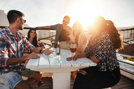 Young people having rooftop party in evening
