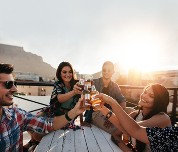 Friends hanging out and enjoying drinks on rooftop party