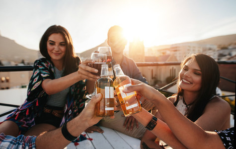 Friends toasting drinks on a rooftop party