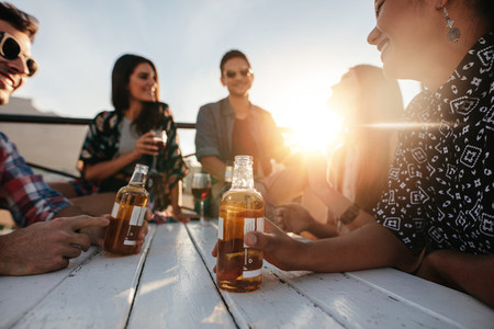 Young people sitting around a table with drinks