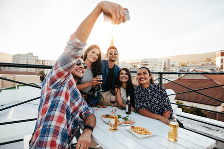 Group selfie at rooftop party