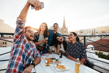 Friends on rooftop party taking selfie