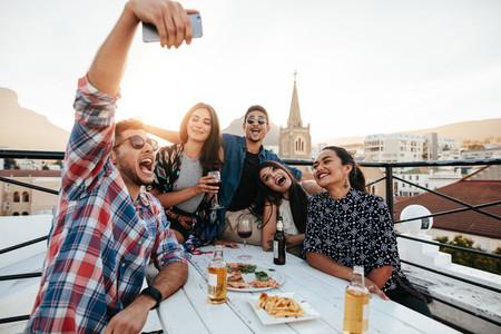 Friends on rooftop party taking selfie