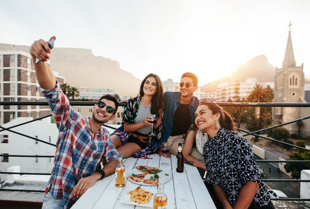 Young people taking selfie on rooftop party