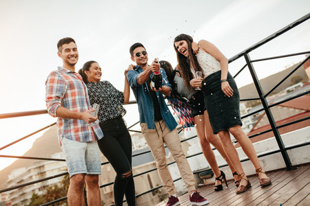 Young people celebrating with champagne at party on rooftop