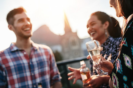 Friends standing together on rooftop with drinks