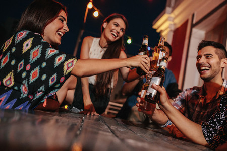 Group of friends toasting drinks at party in evening