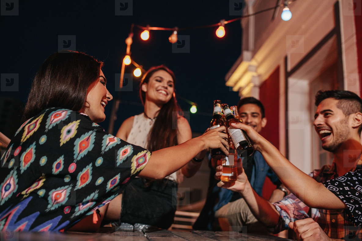 Young people at party toasting beers